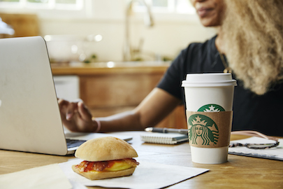 Woman with coffee and sandwich in front of computer